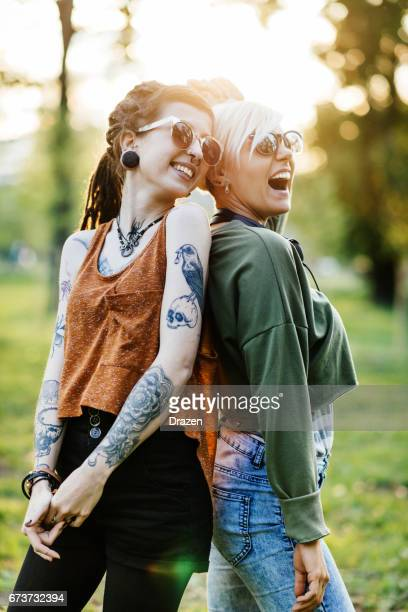 Two women having fun together in park on sunny summer day