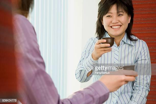 Two women having tea in a business meeting