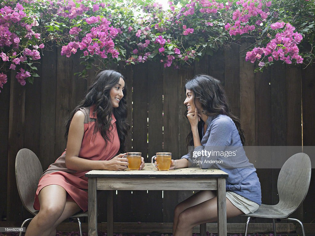 Two women having tea in back yard : Stock Photo