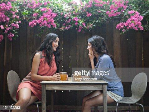 Two women having tea in back yard : Stock Photo