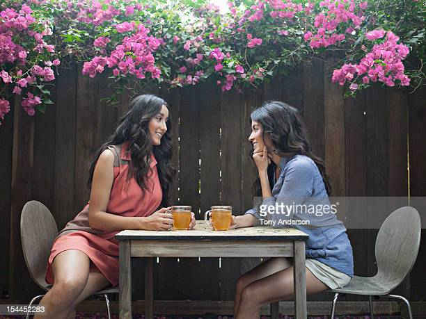 Two women having tea in back yard