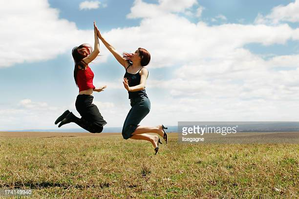 Two women high-fiving in a meadow