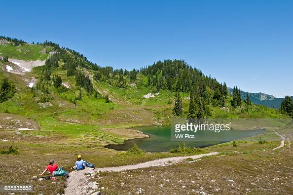 Two women hikers having lunch at Heart Lake High Divide Trail Olympic National Park Washington