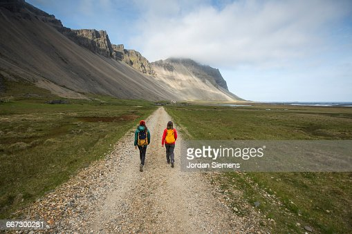 Two women hiking down a dirt road