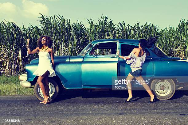 Two women hitchhiking beside their old fashioned car