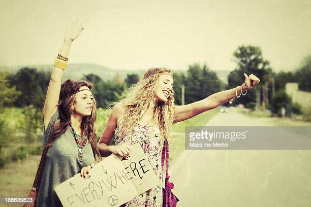 Two women hitchhiking holding 'Everywhere' sign
