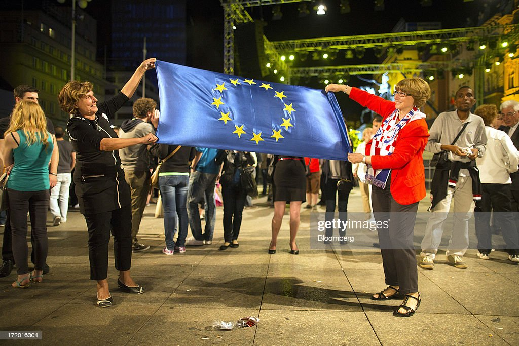 Two women hold a European Union (EU) flag during celebrations in Ban Jelacic square as Croatia marks it's entry into the European Union (EU) in Zagreb, Croatia, on Sunday, June 30, 2013. Croatia will become the European Union's 28th member at midnight, the bloc's first addition since Bulgaria and Romania joined in 2007. Photographer: Simon Dawson/Bloomberg via Getty Images