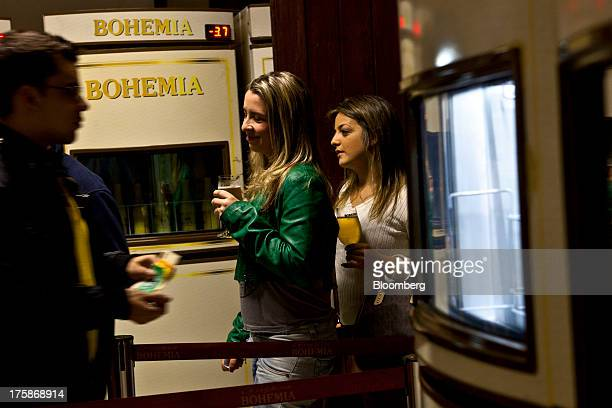 Two women hold glasses of Cia de Bebidas das Americas Bohemia brand beer while a man prepares to pay his bill at a restored Bohemia brewery in...