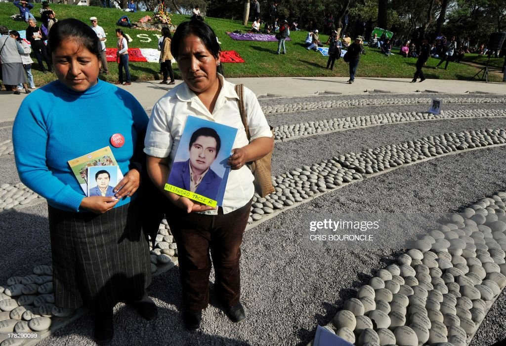 Two women hold portraits at a symbolic graveyard of stones reading names of victims of the war against terrorist groups as The Shinning Path and the Tupac Amarus during the 80's and 90's, in Lima on August 28, 2013. Relatives of victims commemorate the 10th anniversary of the release of the report of the Commission of Truth and Reconciliation of Peru, which concluded that there were 69.000 people killed or missing during the 80's and 90's.