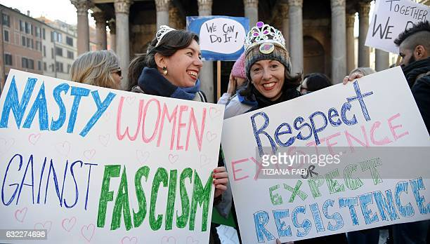 Two women hold signs during a rally against US newly swornin President Donald Trump in Rome on January 21 a day after Trump's inauguration Hundreds...