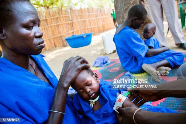 Two women hold their acute malnourished children on March 4 in a stabilisation centre in Ganyiel Panyijiar county in South Sudan South Sudan was...