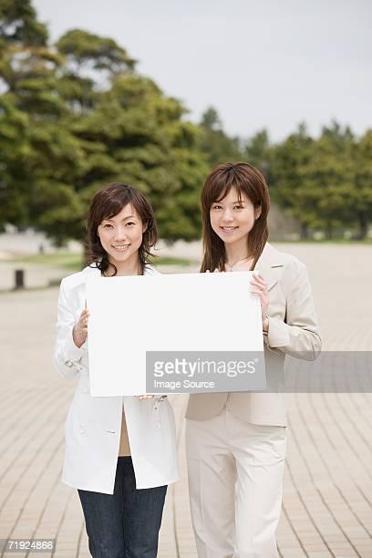 2 人の女性が、ブランクサインを