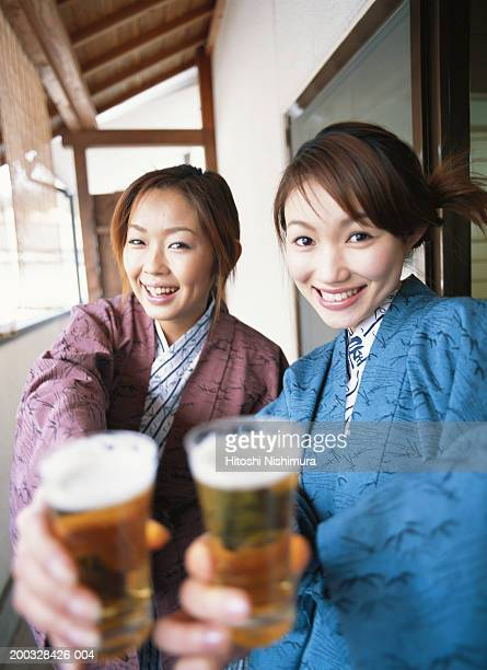 Two women holding beer glass, smiling, portrait