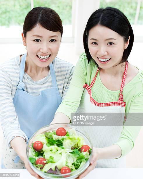 Two Women Holding Bowl Of Salad