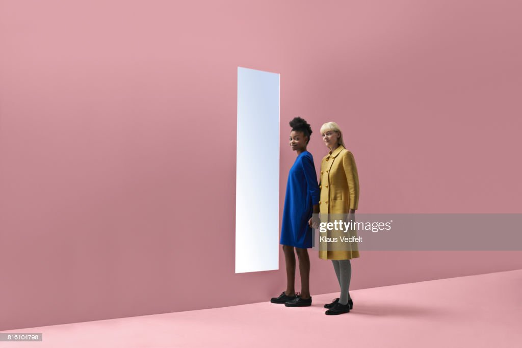 Two women holding hands, standing in front of rectangular opening in coloured wall : Stock Photo