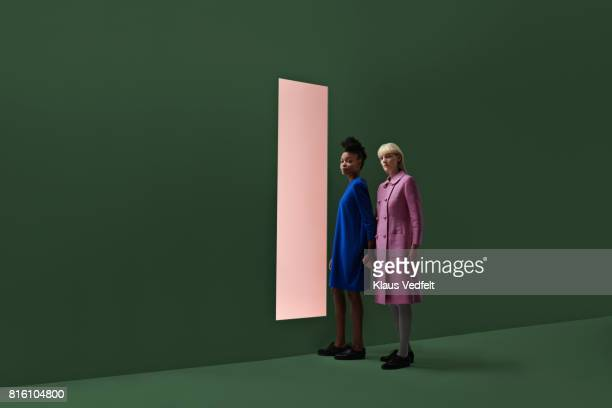 Two women holding hands, standing in front of rectangular opening in coloured wall