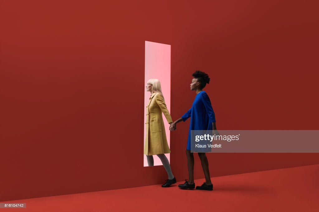 Two women holding hands, walking threw rectangular opening in coloured wall : Stock Photo