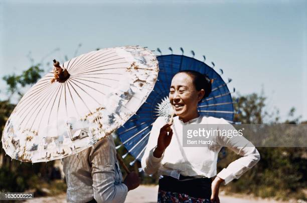 Two women holding parasols Myanmar circa 1950 Original publication Picture Post 4748 Burma