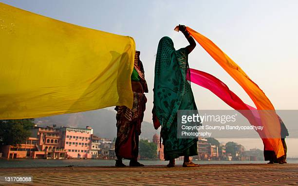 Two women holding saris