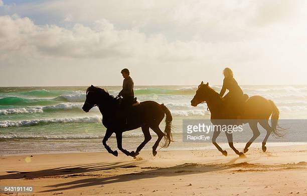 Two women horseriders galloping along wintry beach, almost in silhouette
