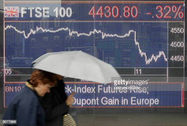 Two women huddle under an umbrella while passing a board showing the FTSE index in west London 12 March 2004 The financial markets were badly hit and...