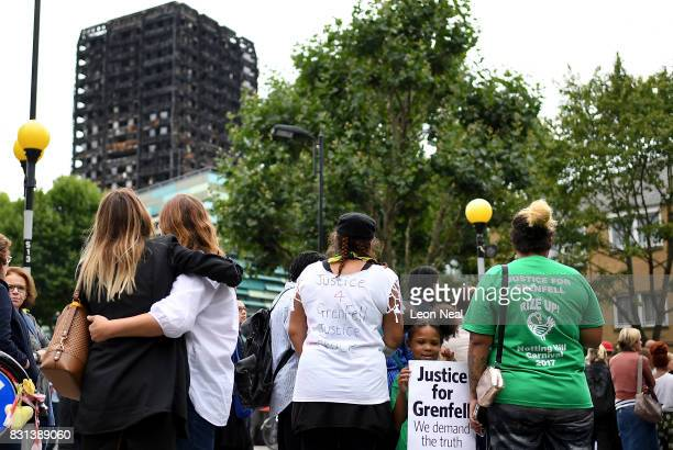 Two women hug as a girl holds a placard reading 'Justice for Grenfell we demand the truth' during a silent march to mark the two month anniversary of...