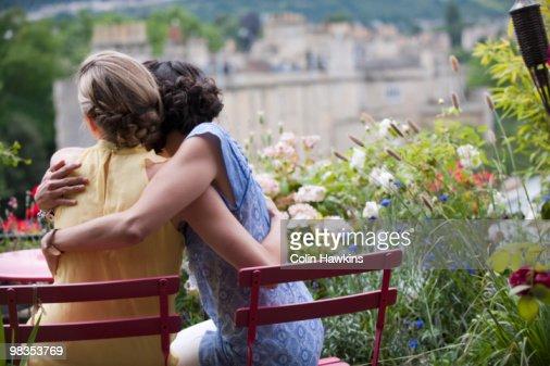 two women hugging on balcony