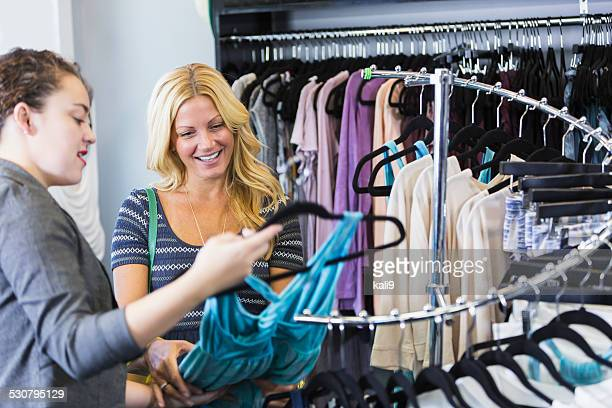Two women in a clohting store looking at a dress