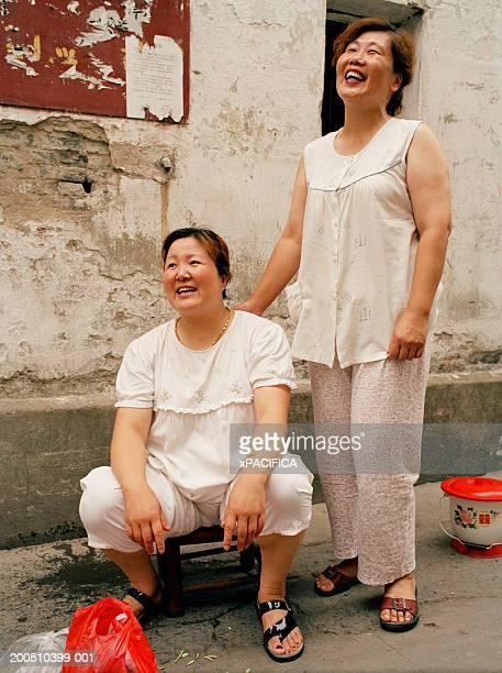 Two women in alley wearing sleepwear, laughing