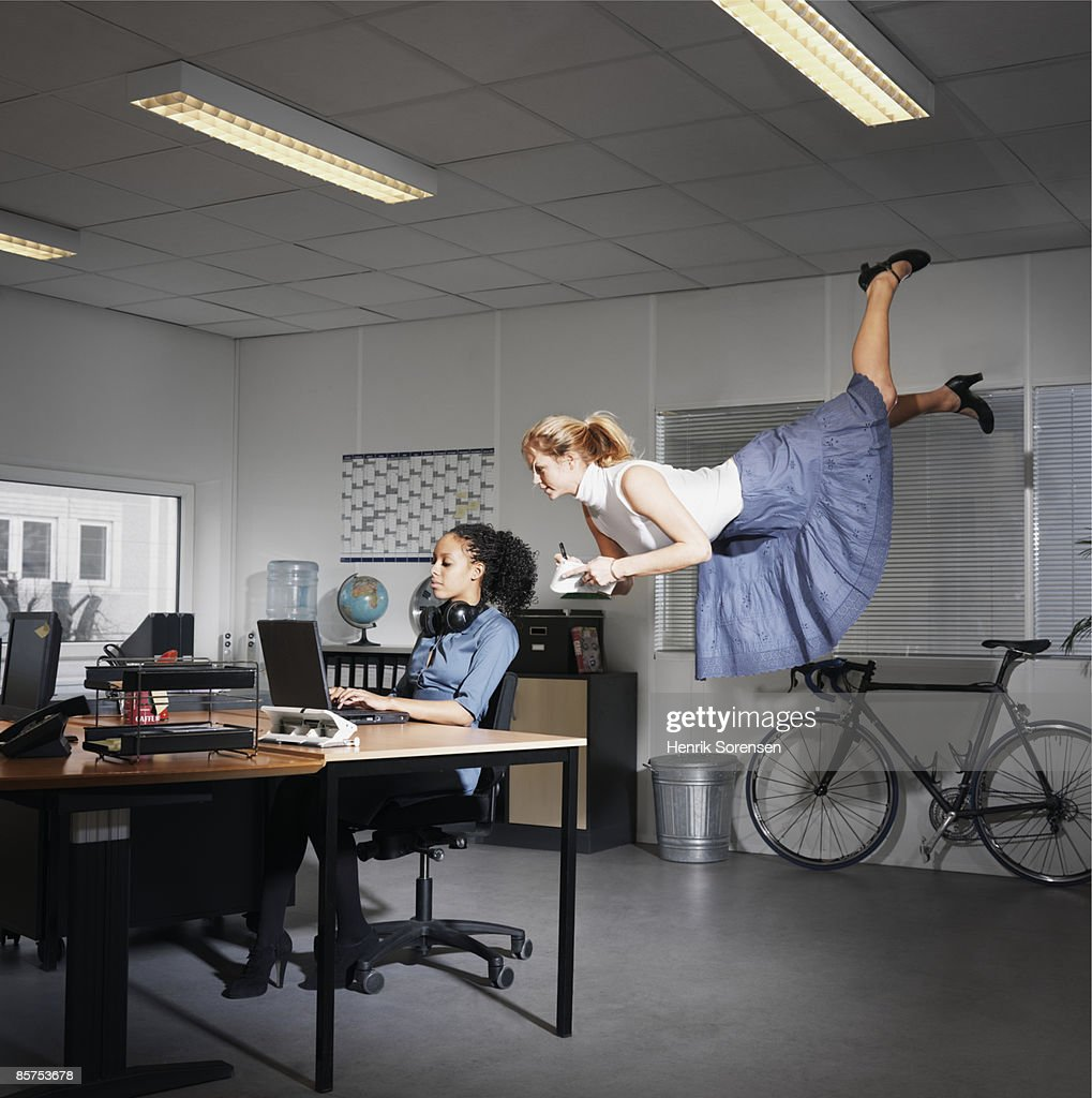Two women in an office, one sitting and one floati