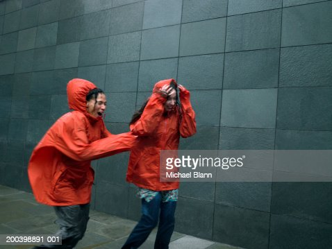 Two women in anoraks struggling to walk against rainstorm, eyes closed
