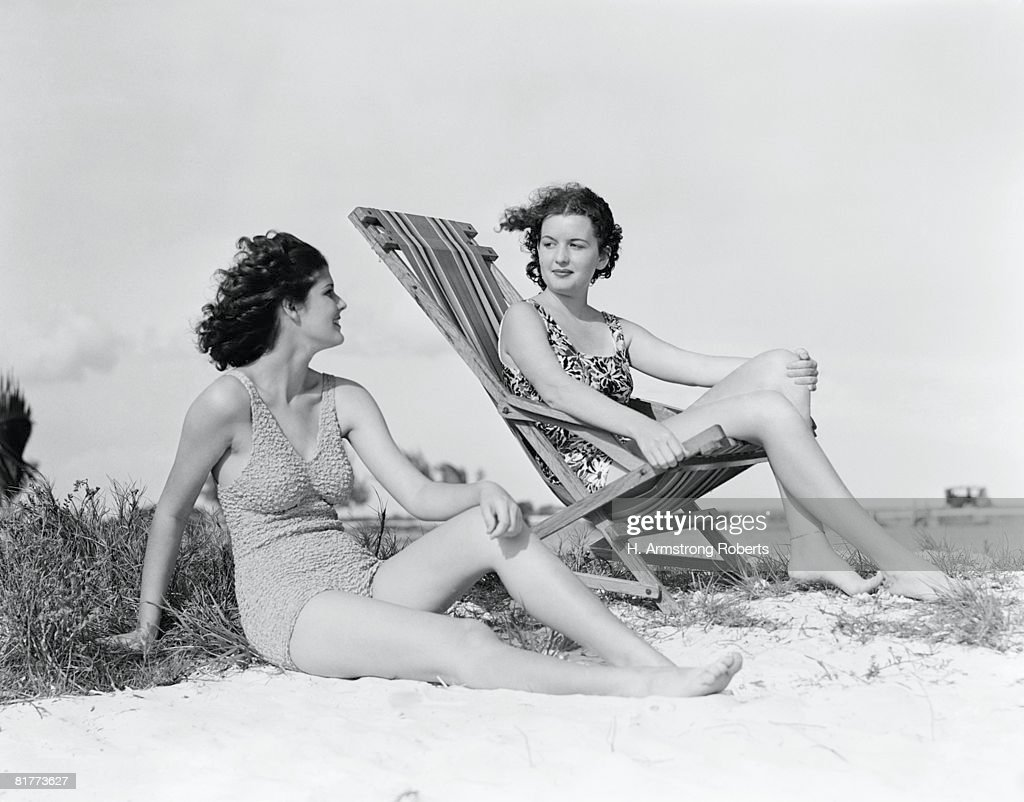 Two women in bathing suits on windy beach. : Stock Photo