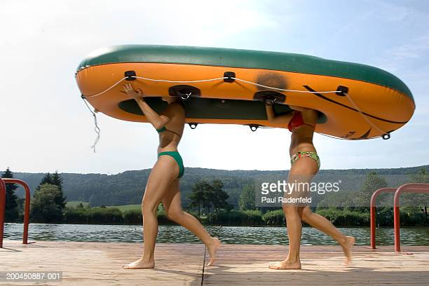 Two women in bikinis carrying dinghy overhead, side view