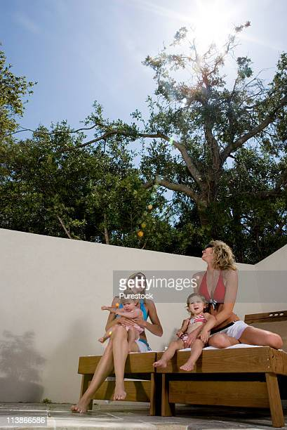 Two women in bikinis with babies sitting in shade on deck chairs