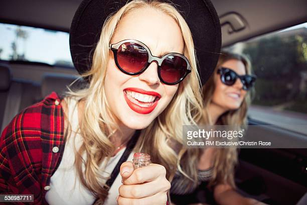 Two women in car wearing sunglasses