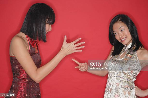 Two women in cheongsams, playing hand game