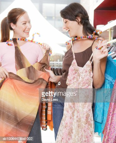 Two women in clothes shop holding dresses, laughing : Stock Photo