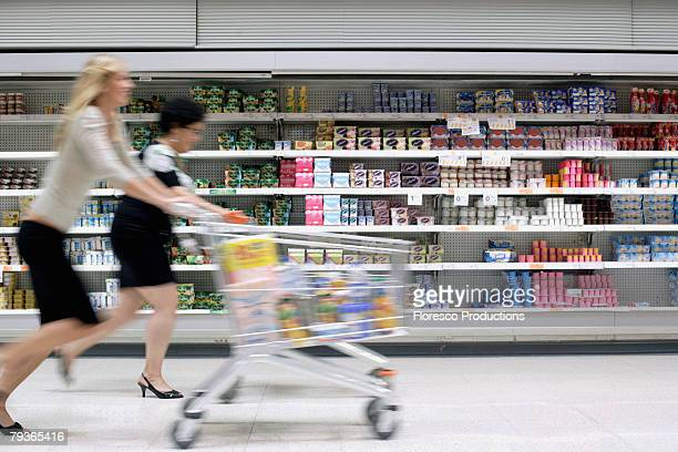 Two women in drug store running with shopping carts