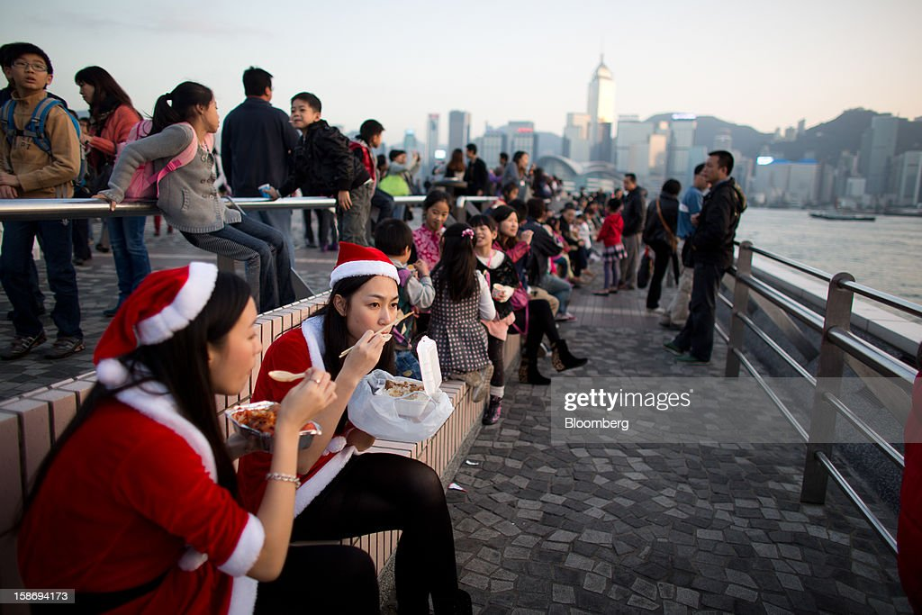 Two women in festive Santa Claus outfits eat their meal on the waterfront promenade in the Tsim Sha Tsui area of Hong Kong, China, on Saturday, Dec. 22, 2012. Hong Kong's economy is set for its weakest annual expansion since the global financial crisis as the European sovereign debt crisis damps global trade. Photographer: Lam Yik Fei/Bloomberg via Getty Images