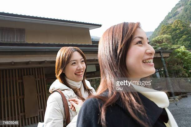 Two women in front of the entrance of Japanese inn, side view, Japan