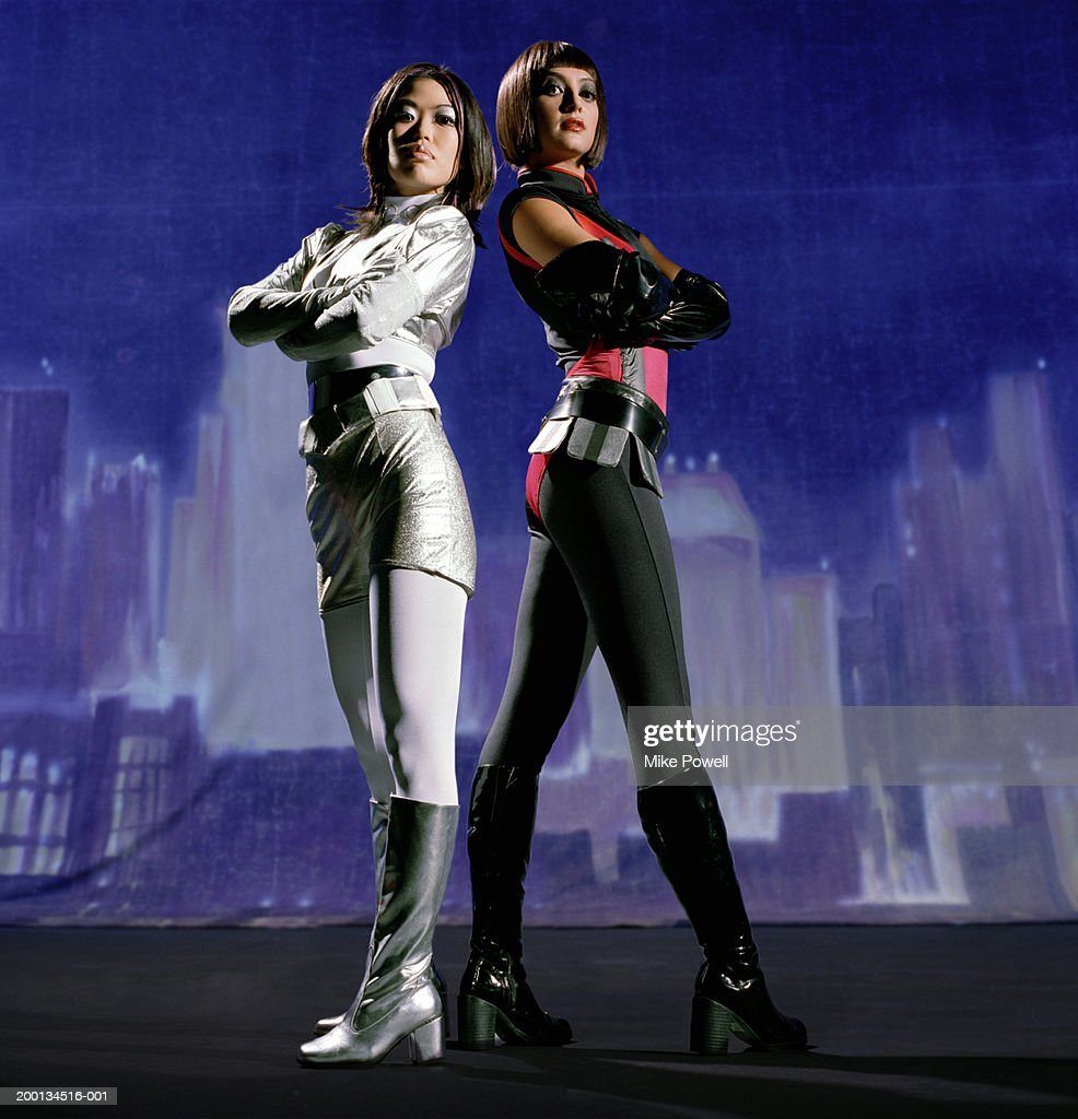 Two women in futuristic costumes, painted skyline in background : Stock Photo