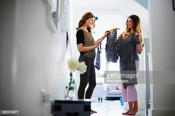 Two women in hallway choosing clothes.
