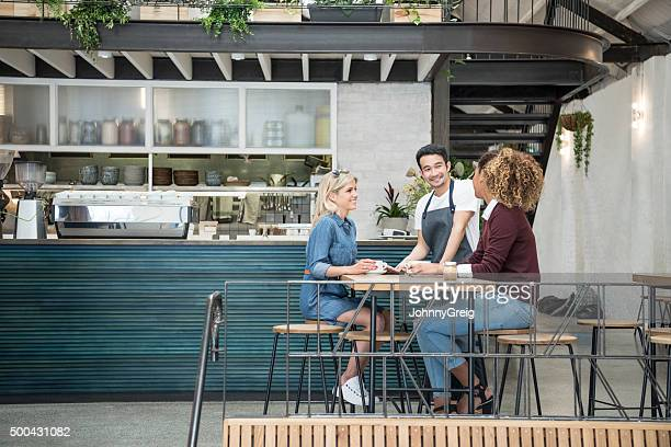 Two women in modern cafe with male waiter