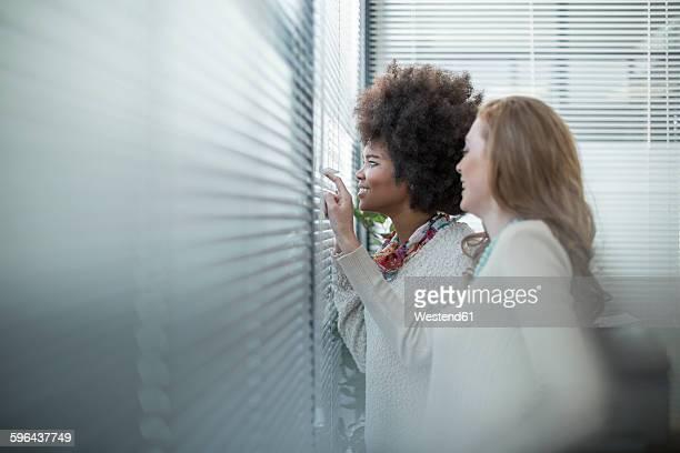 Two women in office looking out of window