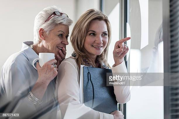 Two women in office looking through blinds