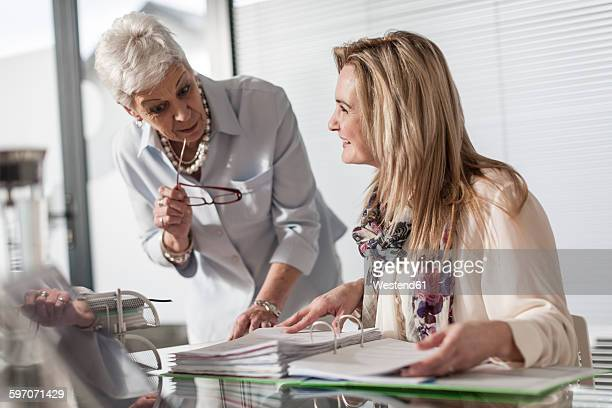 Two women in office working with file folder