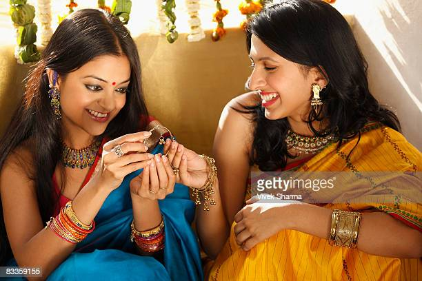 two women in saris, holding jeweled box