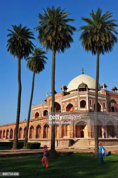 Two women in saris walk across the grass in front of Humayun's Tomb, Delhi, India