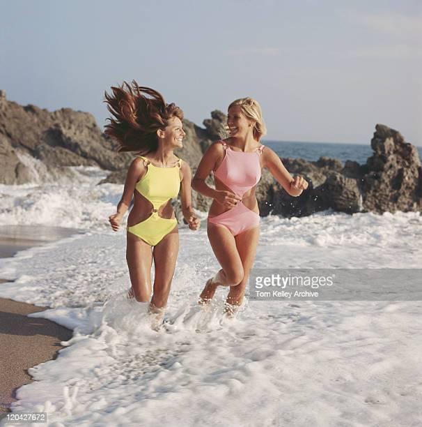 Two women in swimwear running on beach, smiling