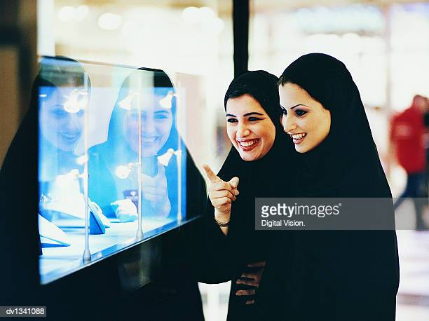 Two Women in Traditional Middle Eastern Dress Looking at a Window Display of a Jewellery Shop in a Shopping Mall